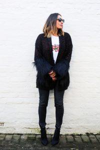 Claire Elizabeth wearing Taylor Morris sunglasses leaning back against a white wall wearing Helen Bridges coatigan