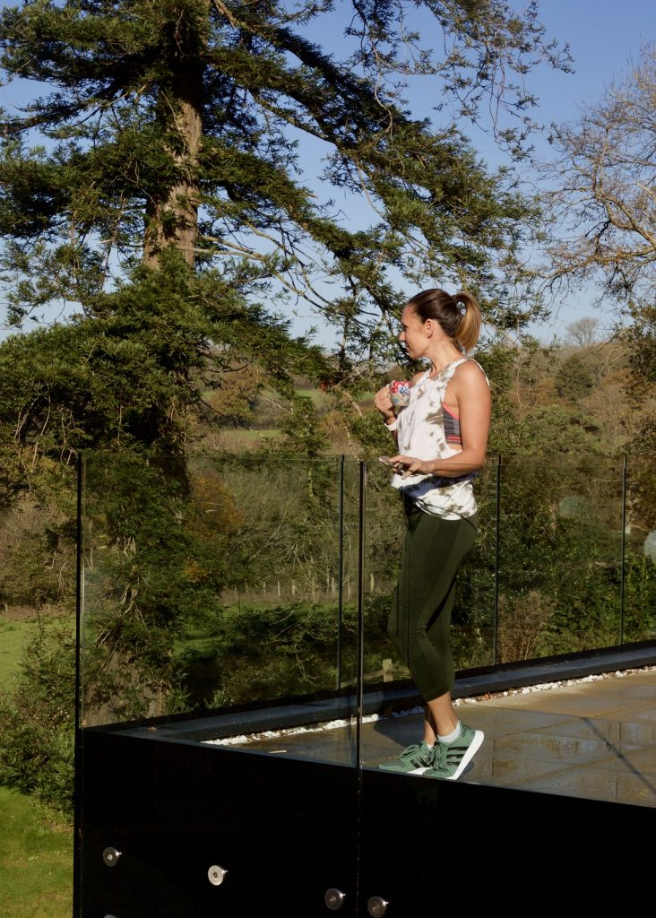 Claire Elizabeth standing on a balcony at Ockenden Manor spa wearing athletic wear by Forever 21