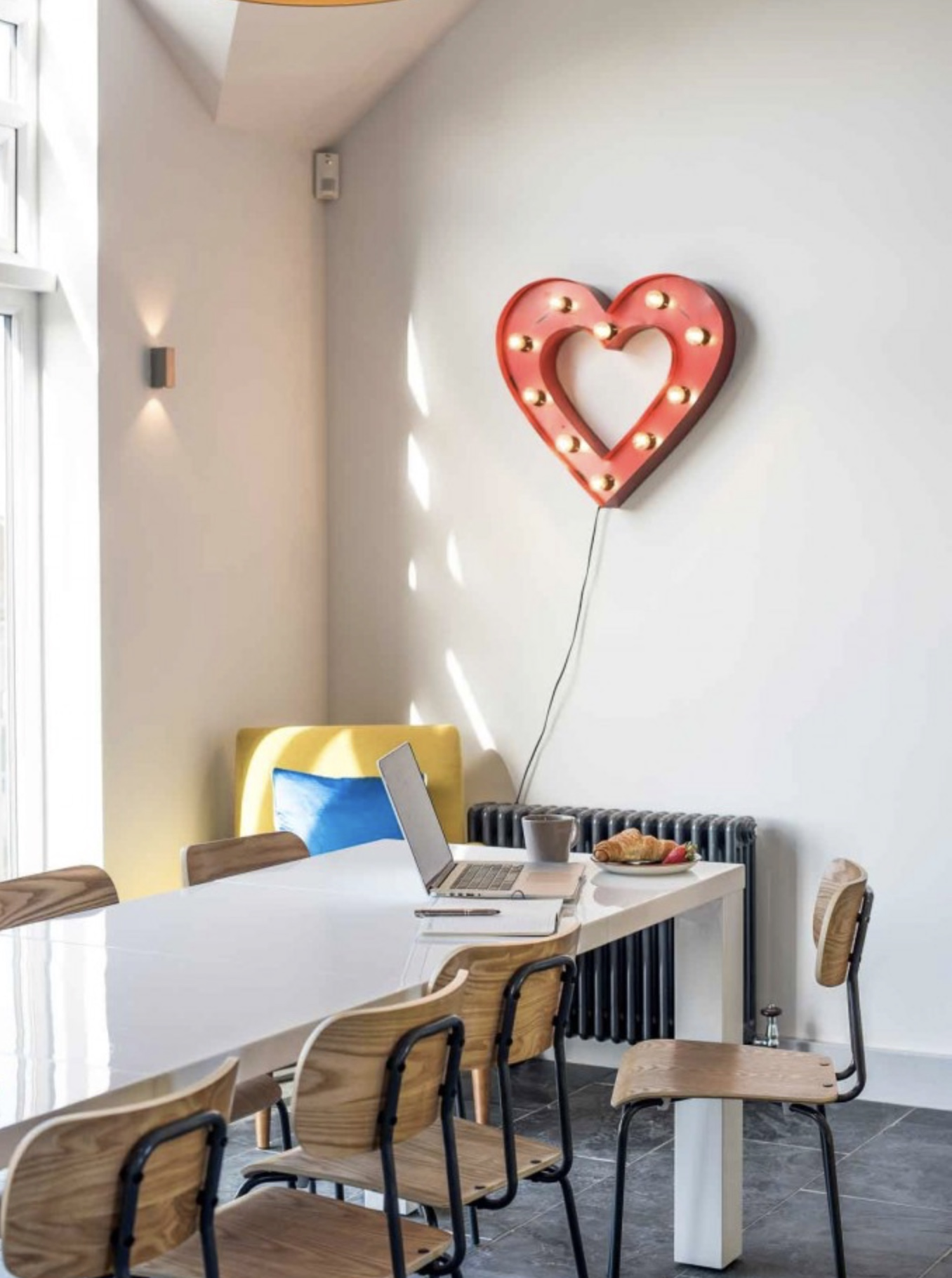 Dining room at Surf Six with wood and yellow chairs and a spotlight red metal heart hanging on the wall