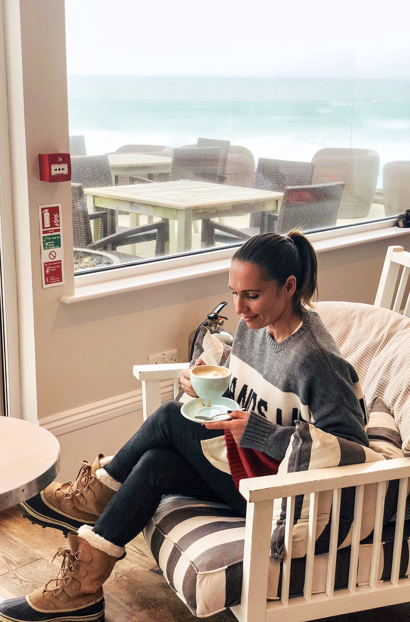 Claire Elizabeth sitting at Watergate Bay hotel sipping a latte while wearing a Hands up in the air slogan Red, white and grey jumper with the Cornish sea in the background