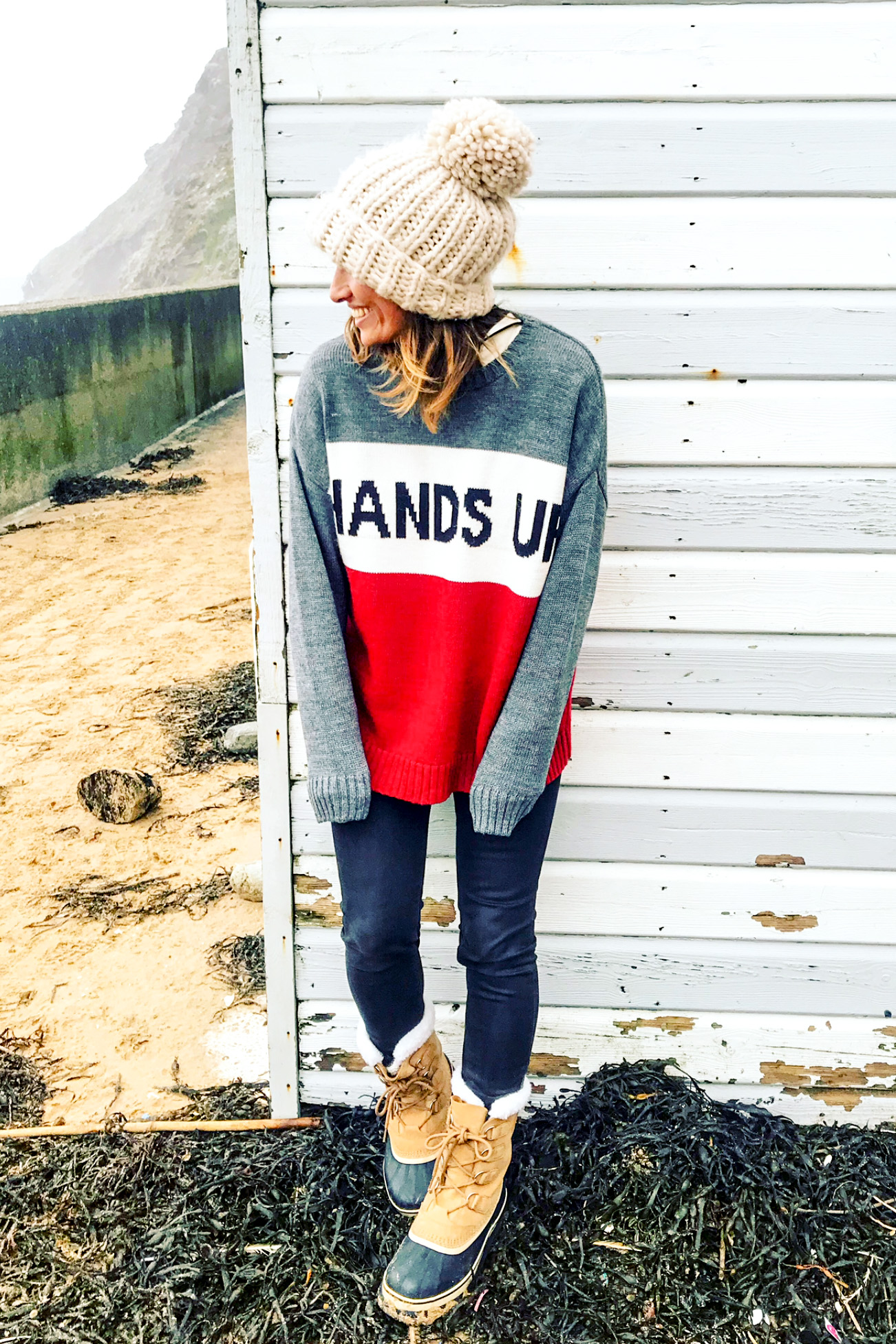 Claire Elizabeth standing with back against a blue and white striped surf hut wearing a hands up in the air slogan knit from Zara menswear and a cream bobble hat