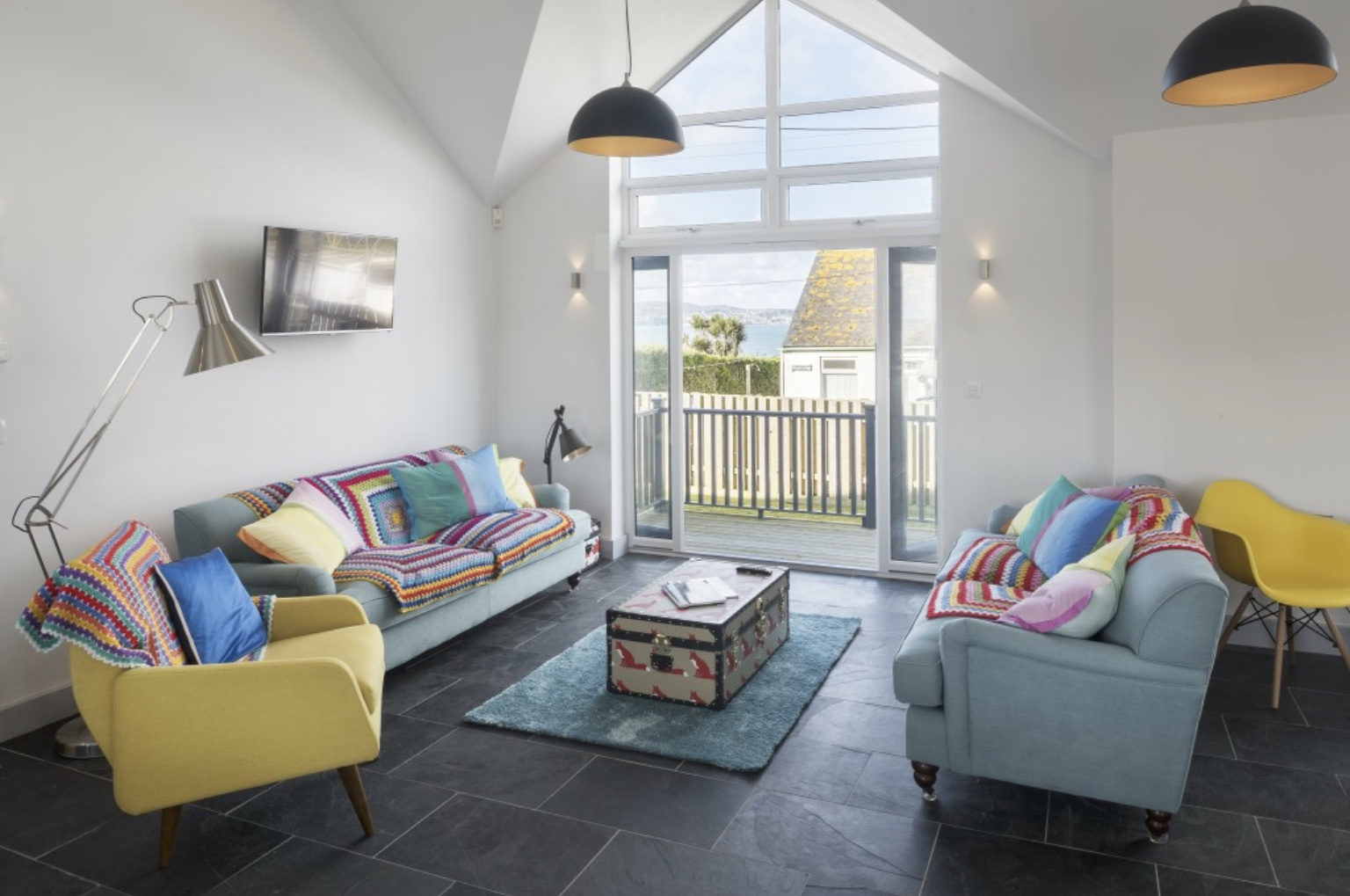 Living area at Surf Six holiday home in Cornwall with sofas and chairs seated around an eclectic coloured trunk and four hanging black and gold pendants
