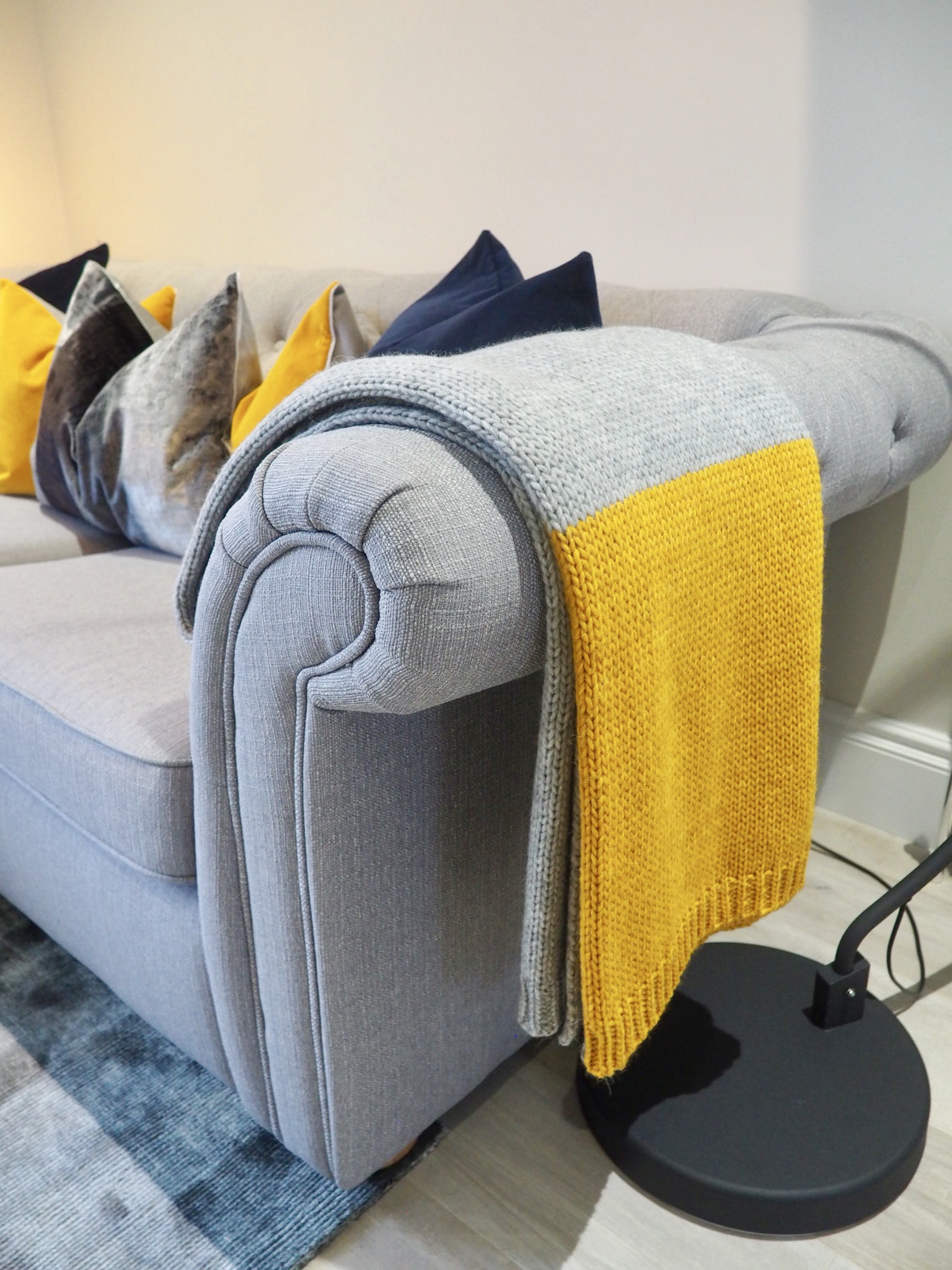 Grey chesterfield sofa with grey and ochre Alpaca throw, and a slection of cushions in navy, ochre and grey velvets