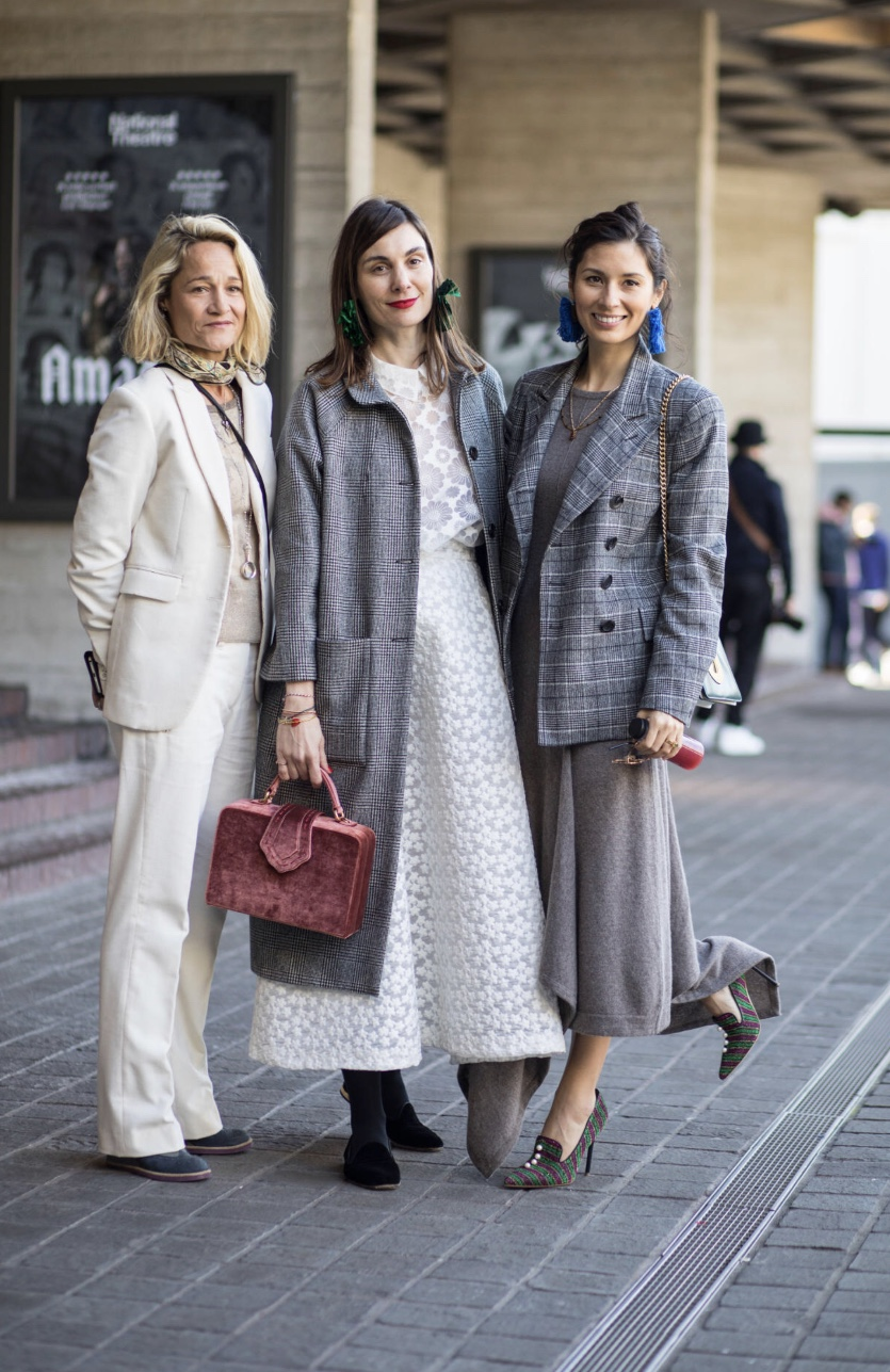 Three fashionistas posing for a photograph at London Fashion Week wearing very fashionable clothes