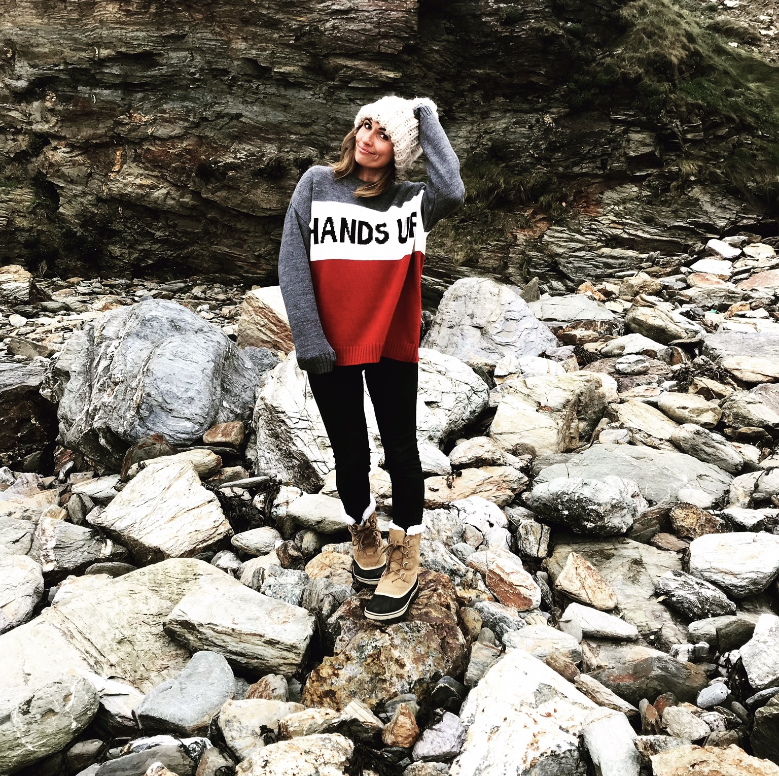 Claire Elizabeth standing on the rocks at Watergate Bay holding her cream bobble hat while wearing Sorel Carabou boots and a Hands Up in the air slogan red, grey and white knit by Zara menswear.