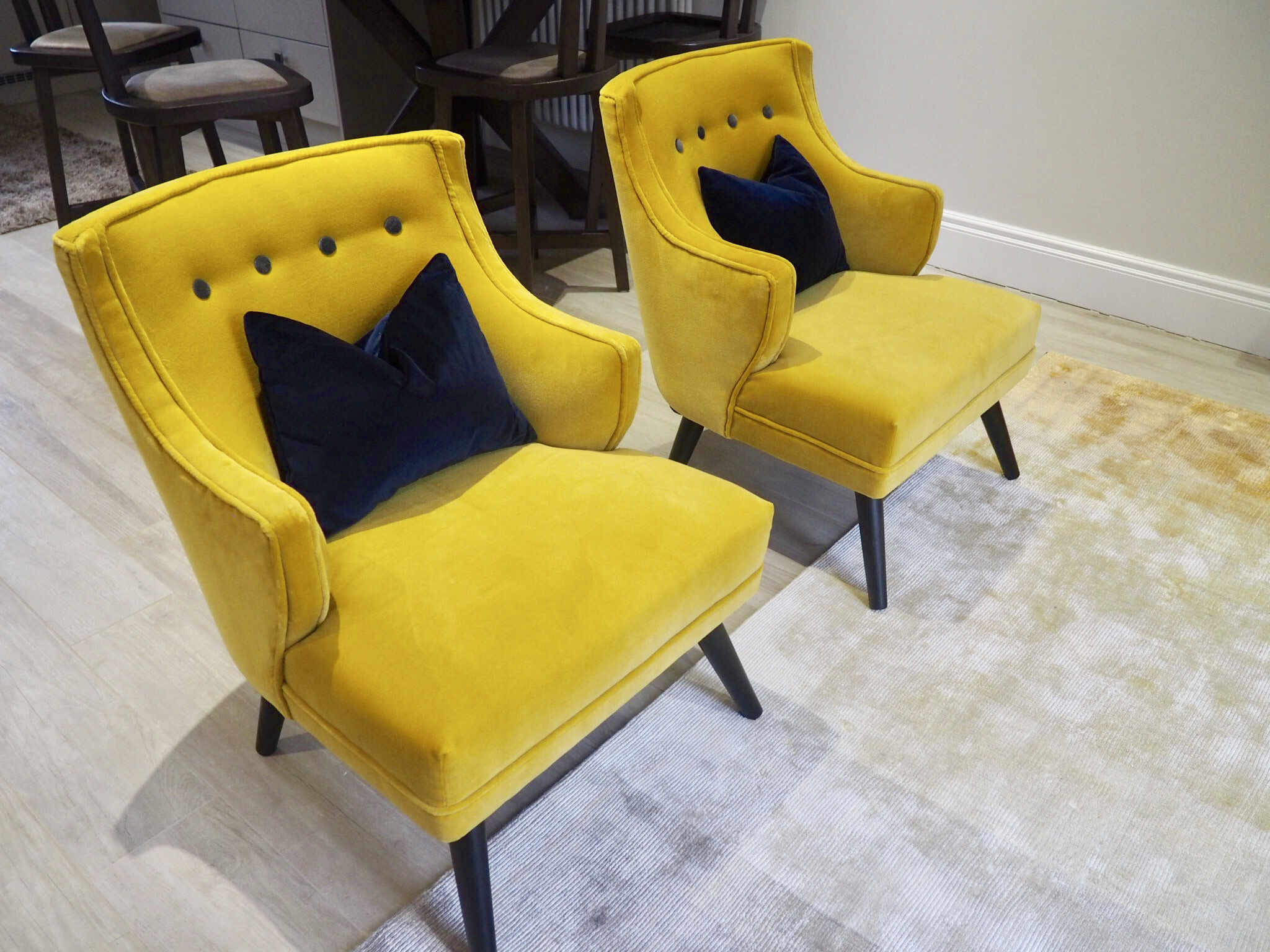 Navy velvet cushions sitting on top of two mustard velvet chairs from Atkin and Thyme