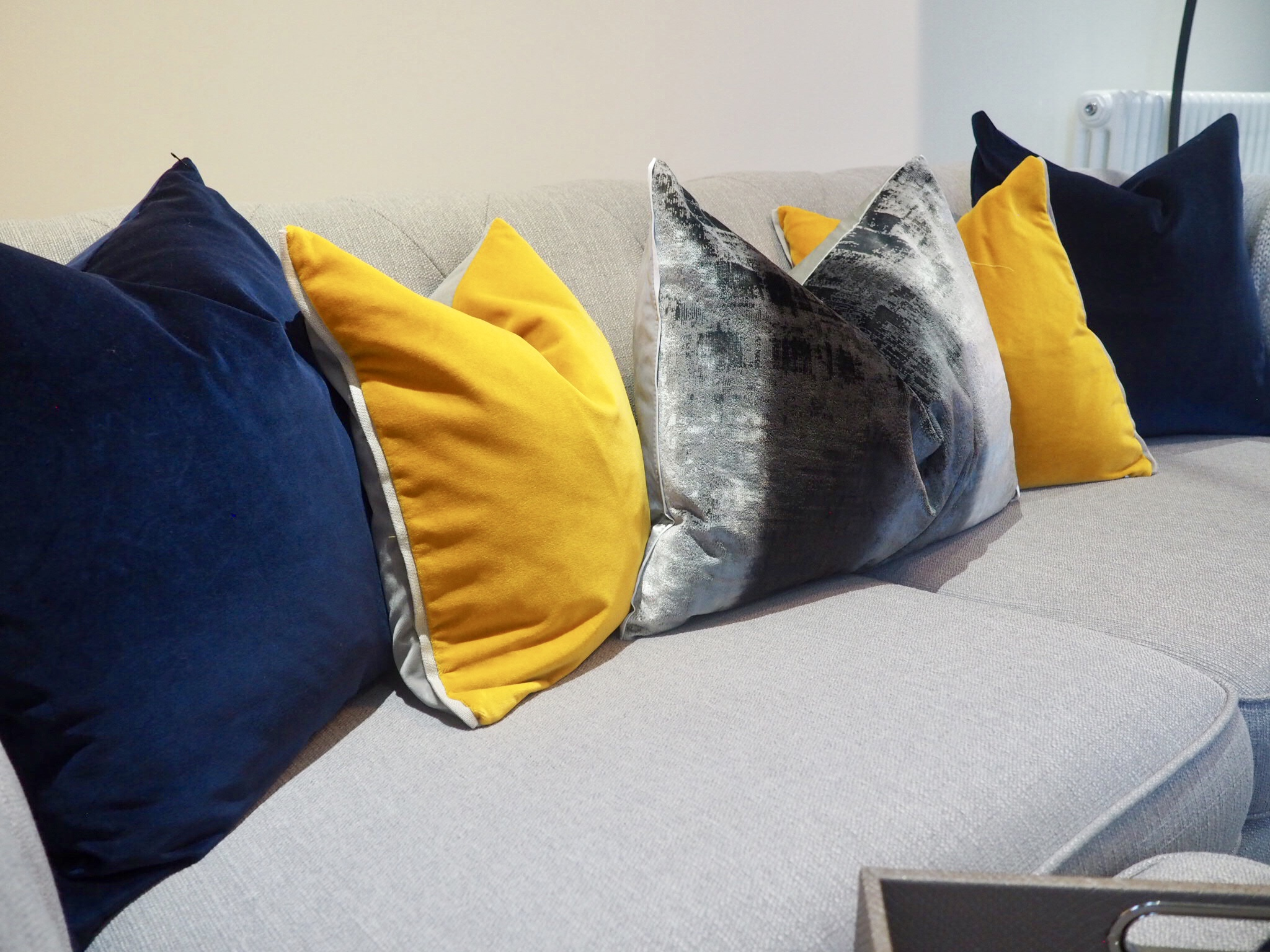 Navy, mustard and grey velvet cushions on top of a grey chesterfield sofa