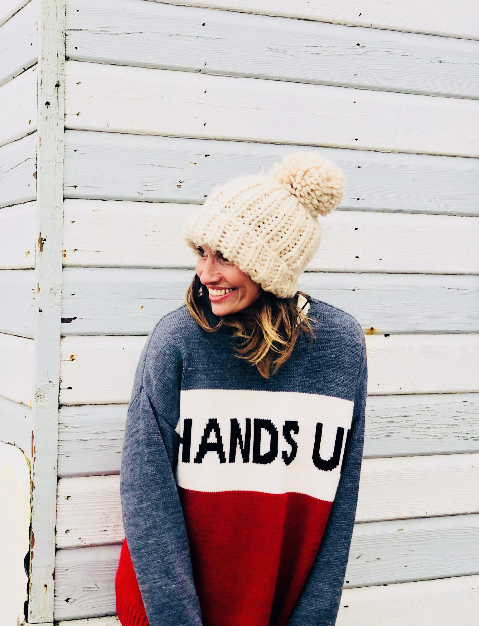 Claire E,izabeth standing with back against a blue and white striped surf hut wearing a hands up in the air slogan knit from Zara menswear and a cream bobble hat