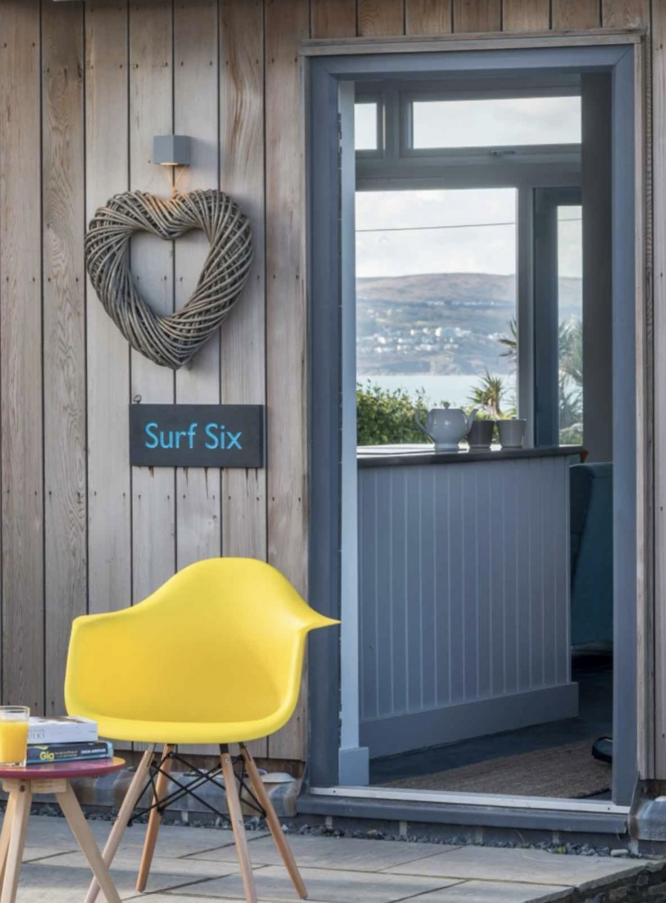 Front door entrance to Surf Six in Cornwall featuring a yellow eames chair and a twine hanging heart