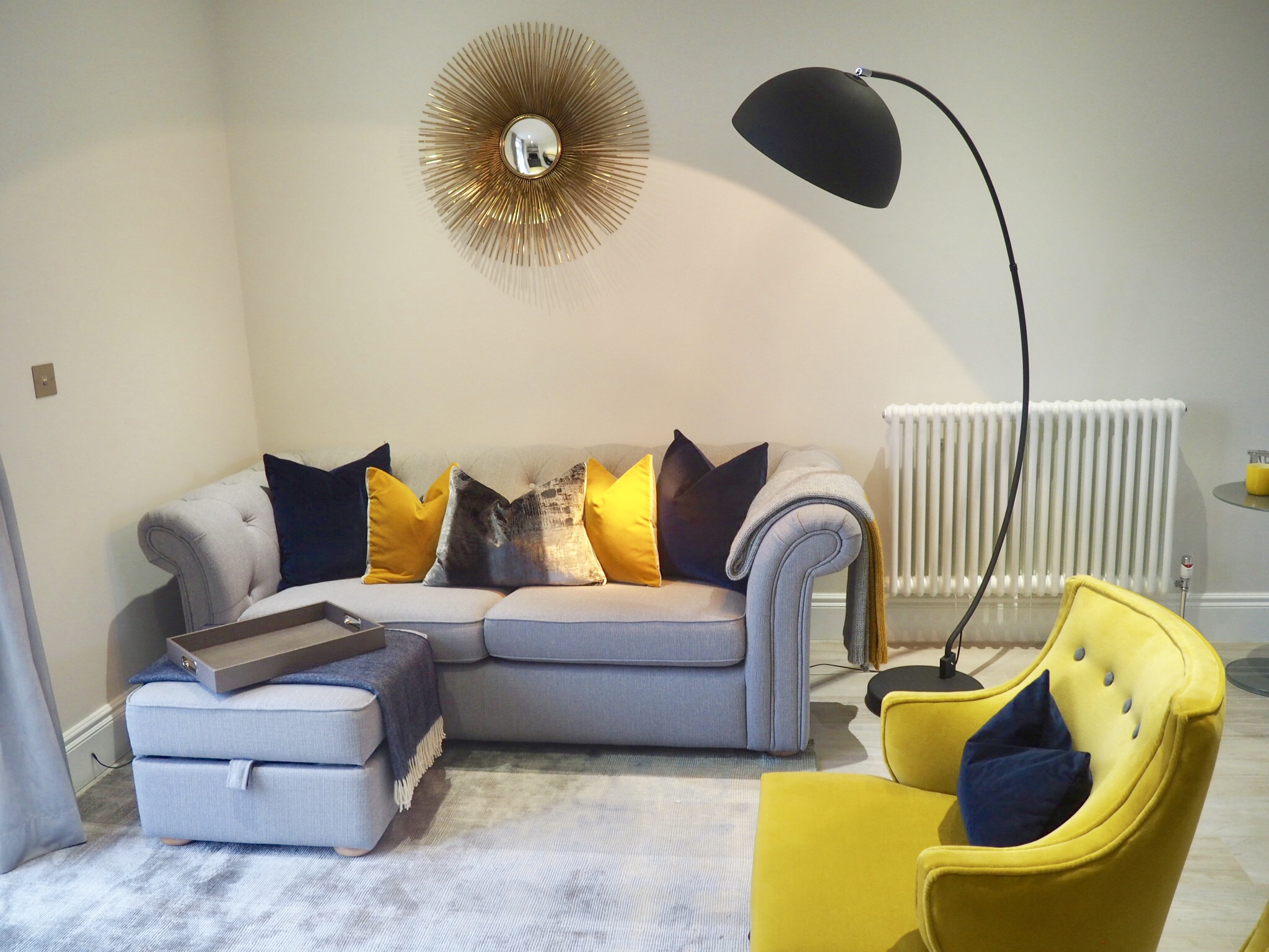 Living room with ombré grey and mustard rug, two mustard coloured chairs and cushions ranging through navy, ochre and grey, with a faux alligator tray.