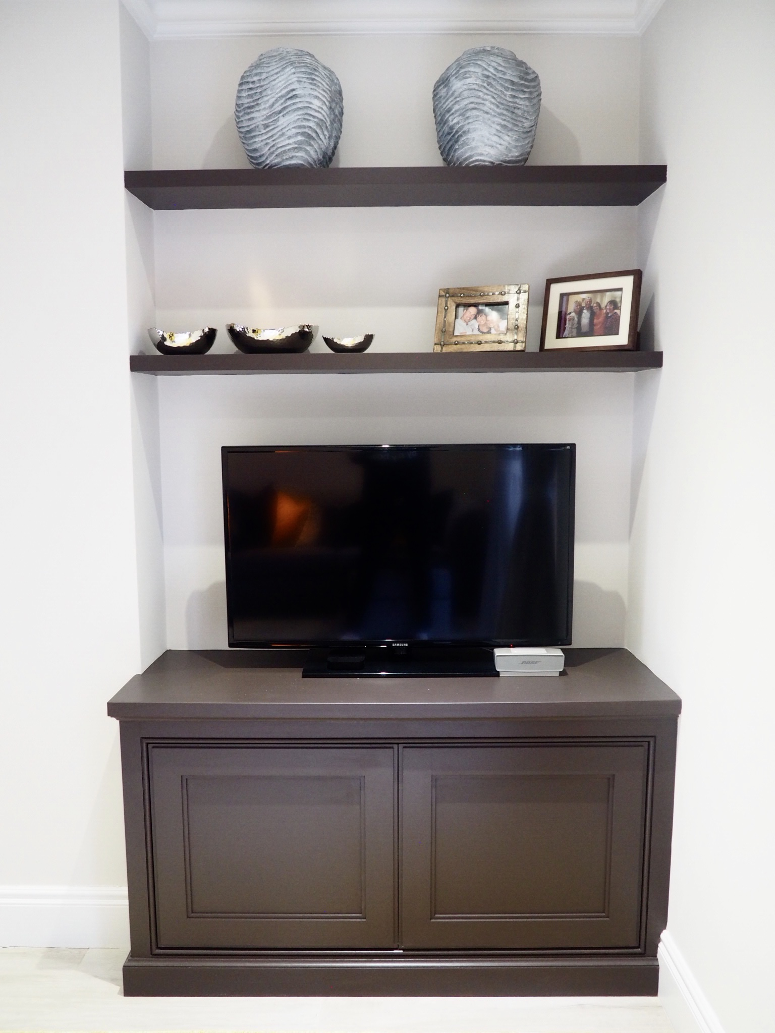 Bespoke media unit with two shelves and silver and copper bowls on the first shelf, and two wavy grey vases on the top shelf