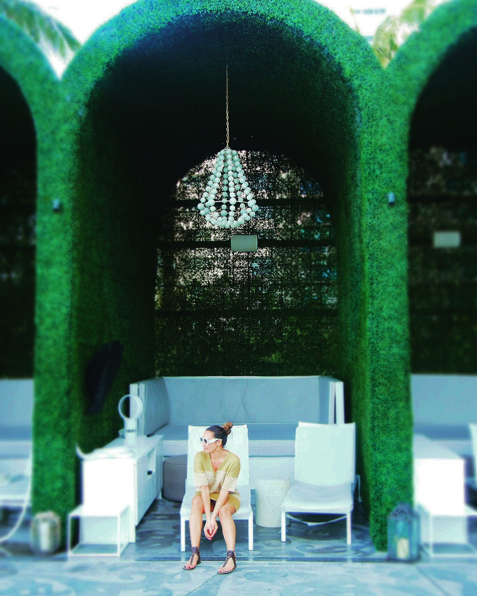 Claire Elizabeth sitting under a clay beaded outdoor chandelier in a faux grass cabana at the Mondrian Hotel South Beach
