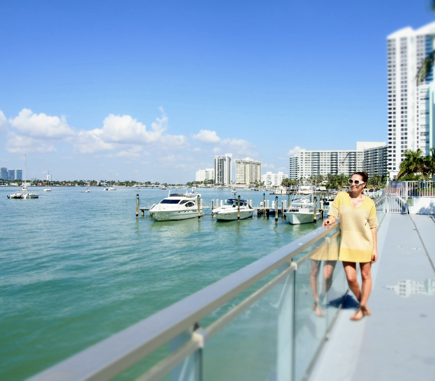 Claire Elizabeth standing in a dress by Zara overlooking Miami Buscayne a Bay at the Mondrian Hotel South Beach
