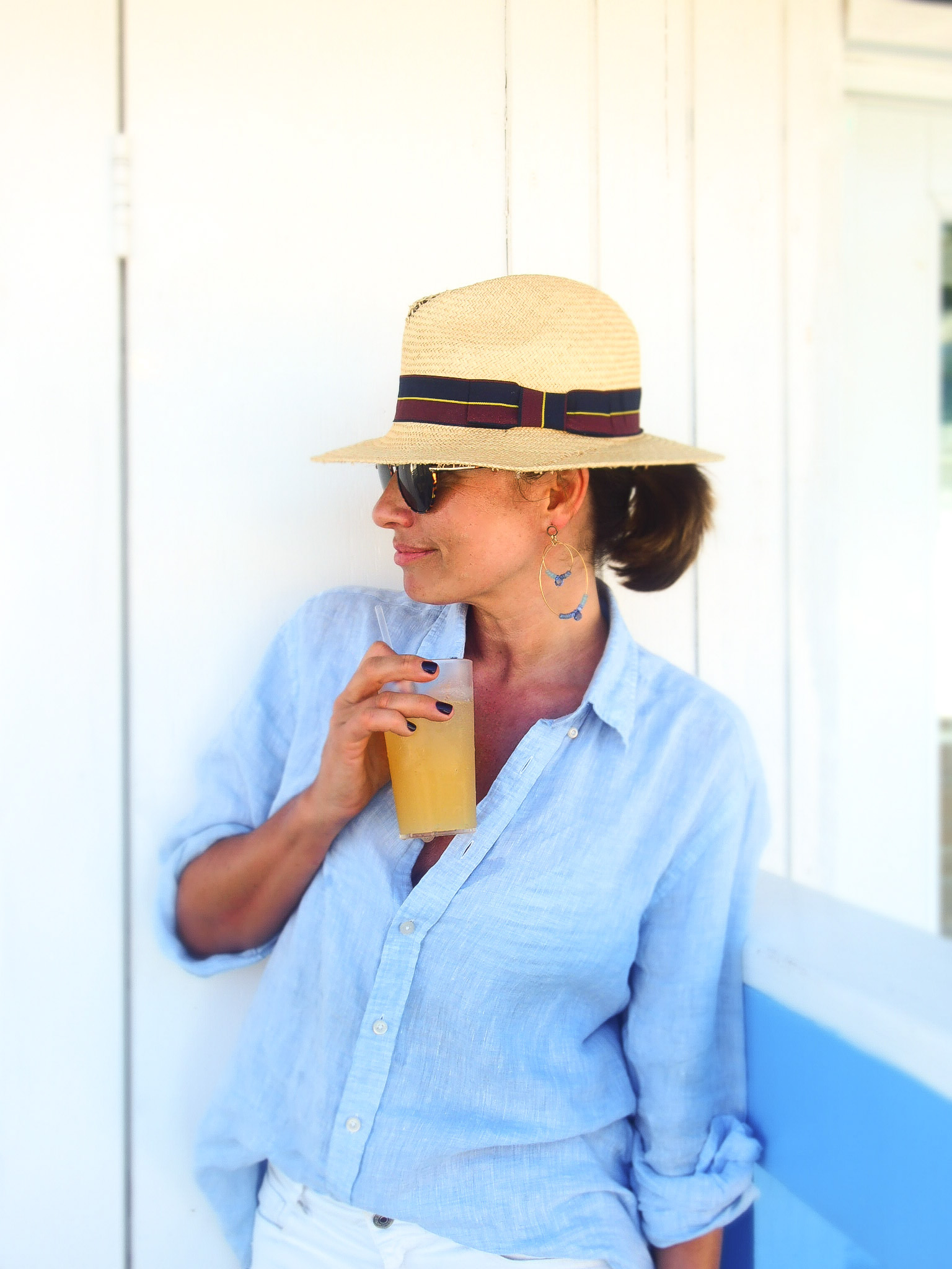 Claire aelizabeth wearing a blue linen shirt wearing earrings by Susan suell and drinking juice while overlooking the ocean
