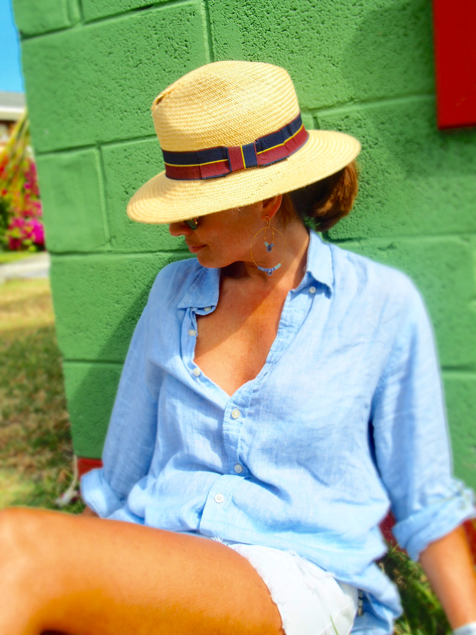Claire Elizabeth sitting on the ground in front of a Caribbean beach hut while wearing earrings by Susan Suell