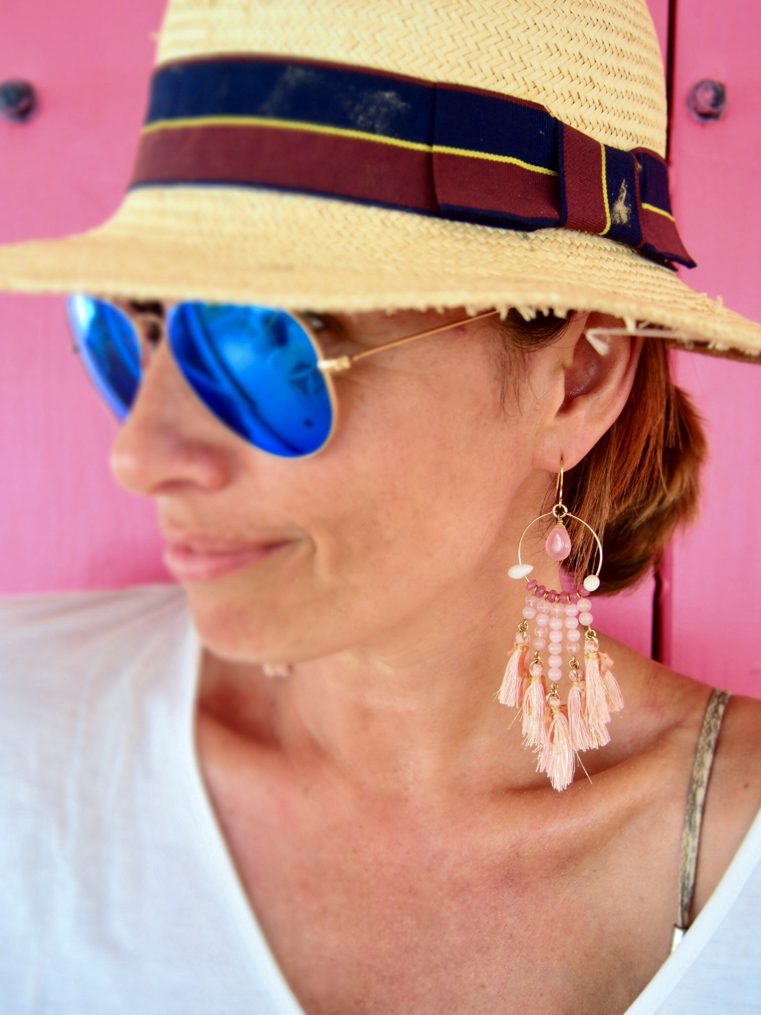 Claire Elizabeth wearing large pink tassel earrings by Susan Suell and blue tinted ray an sunglasses