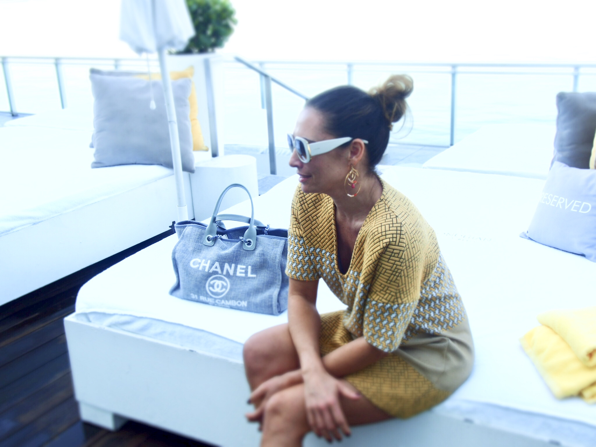 Claire Elizabeth sitting on a sun lounger next to a Blue Chanel Bag in a yellow dress overlooking Miami Biscayne Bay at the Mondrian South Beach