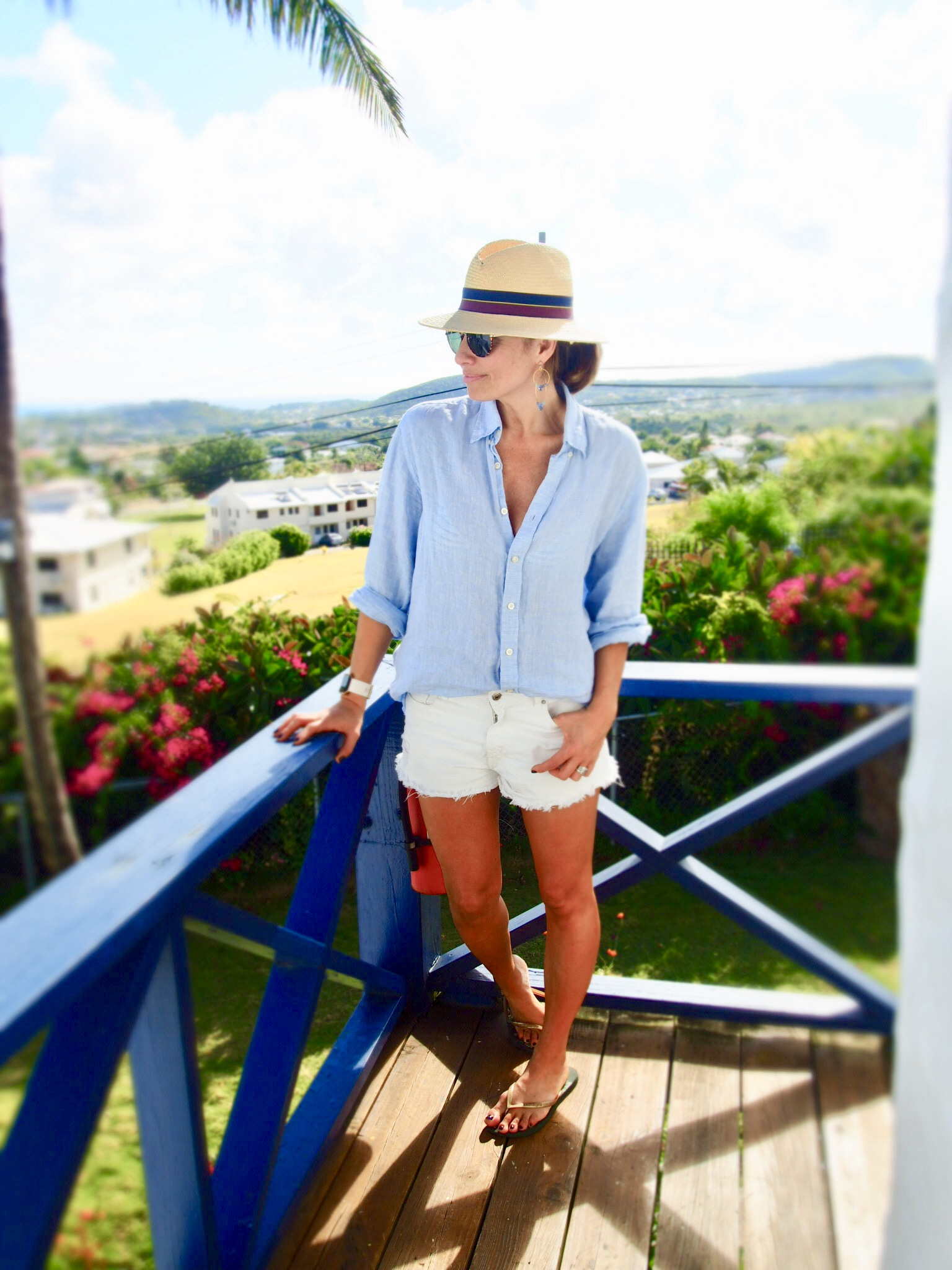 Claire Elizabeth standing on a balcony wearing shorts by Forever 21 and a blue shirt by Hackett, together with a straw Panama hat and earrings by Susan Suell