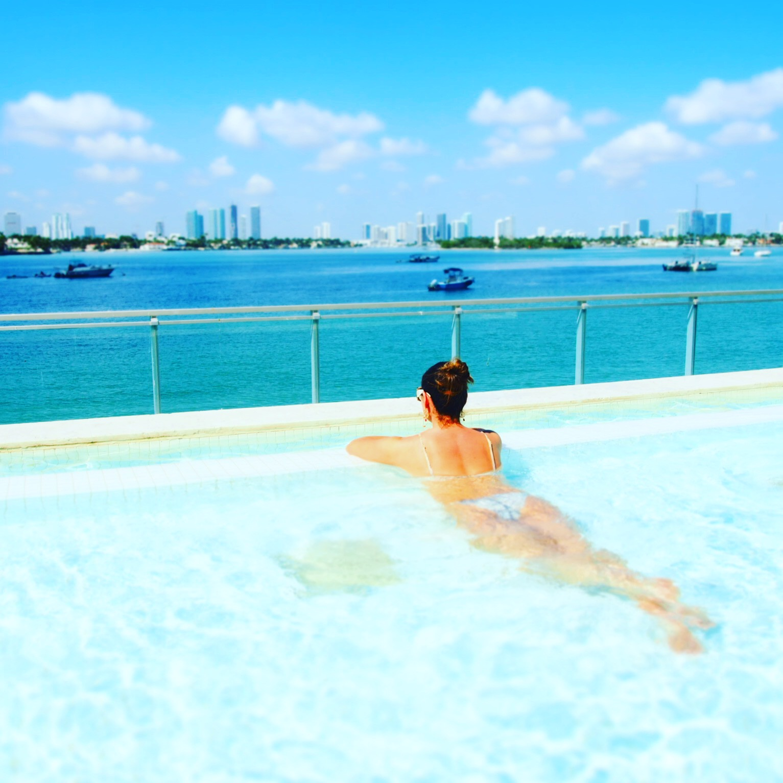 Claire Elizabeth lying in the plunge pool overlooking Biscayne Bay at the Mondrian Hotel South Beach wearing a Melissa Odabash bikini