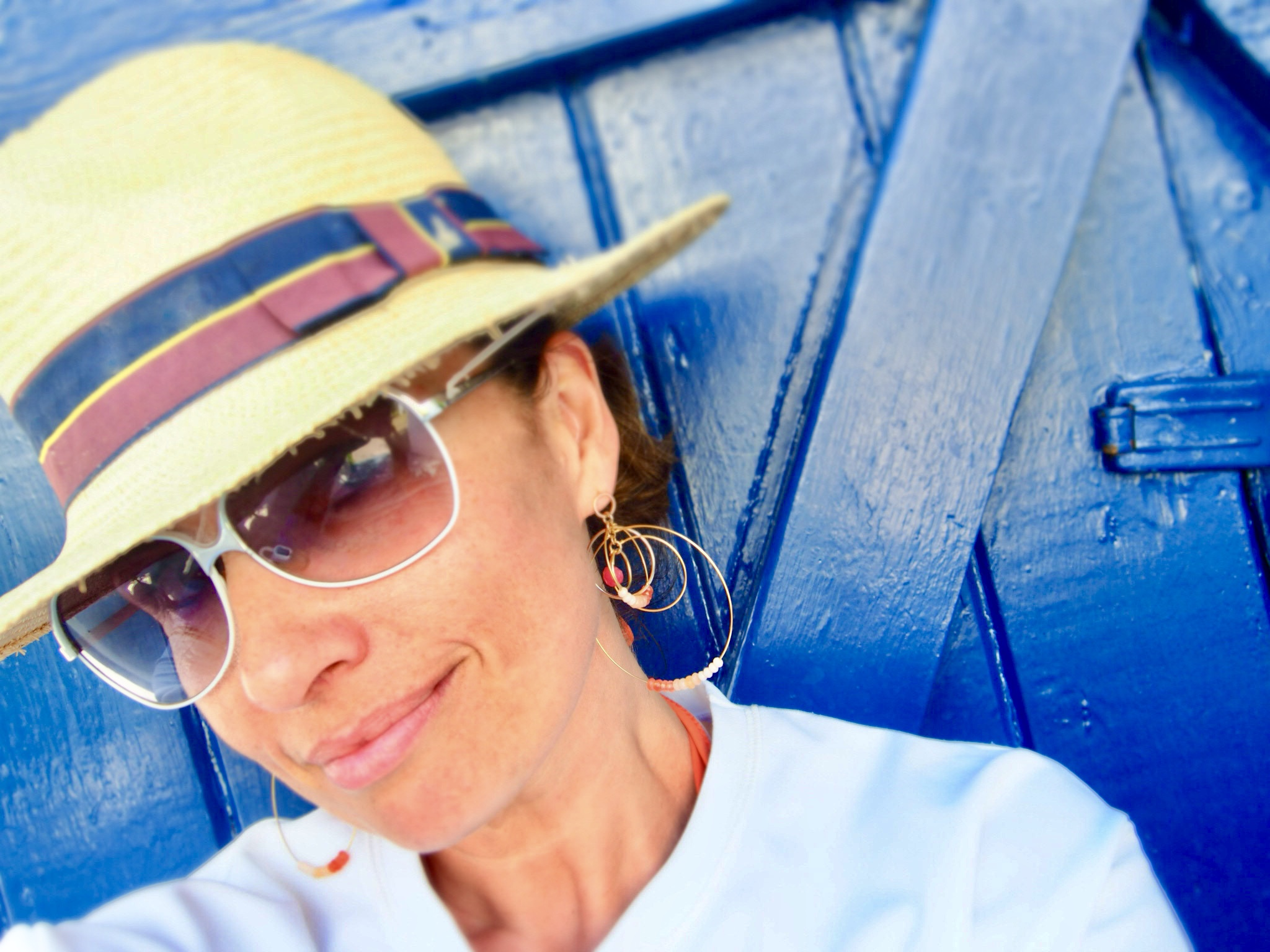 Claire Elizabeth wearing white tinted glasses and leaning up against a bright blue door and wearing gold and pink earrings by Susan Suell