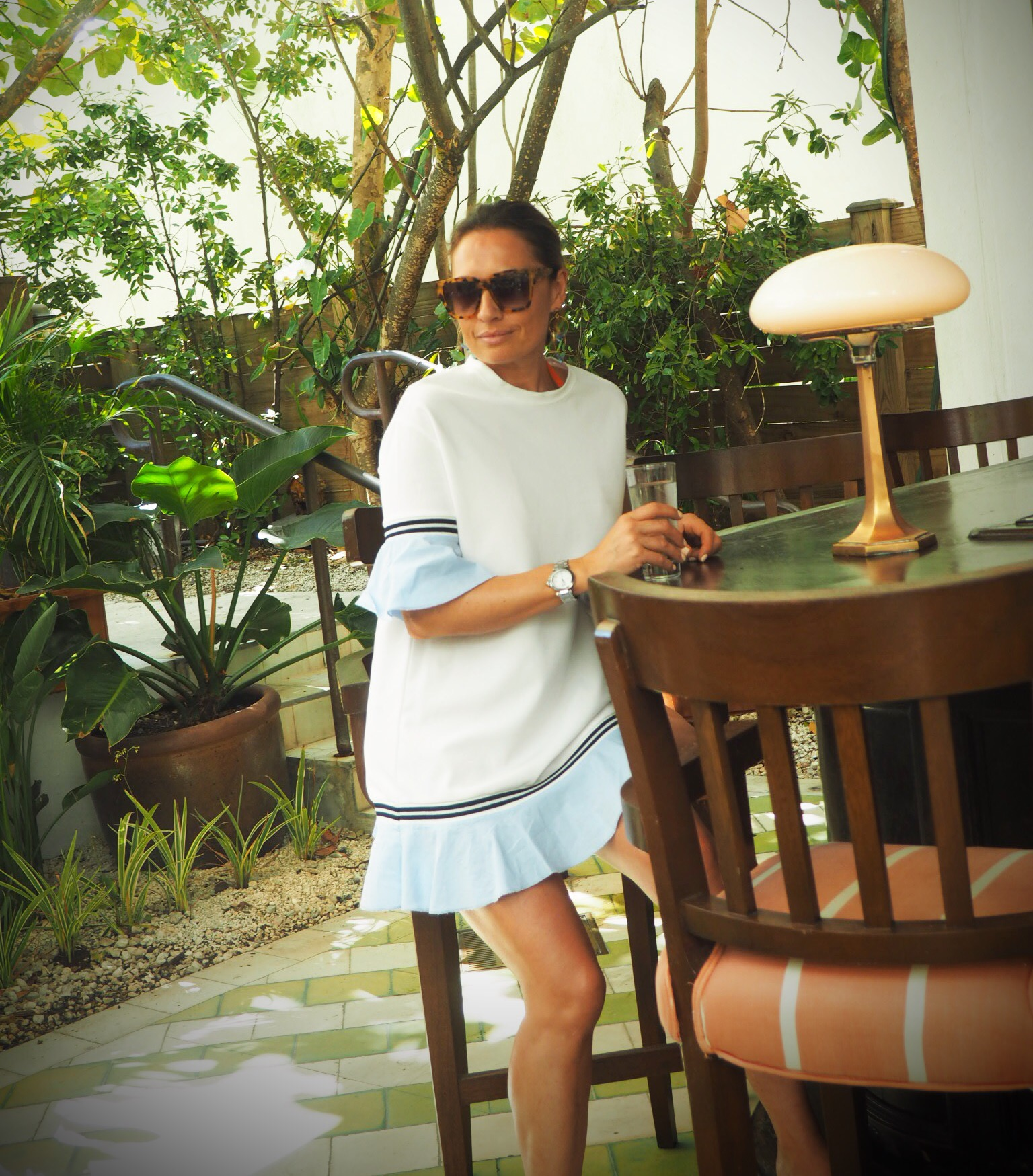 Claire Elizabeth wearing short white tennis style dress with blue cuffs and hemline, sitting at the bar at Soho House in Miami