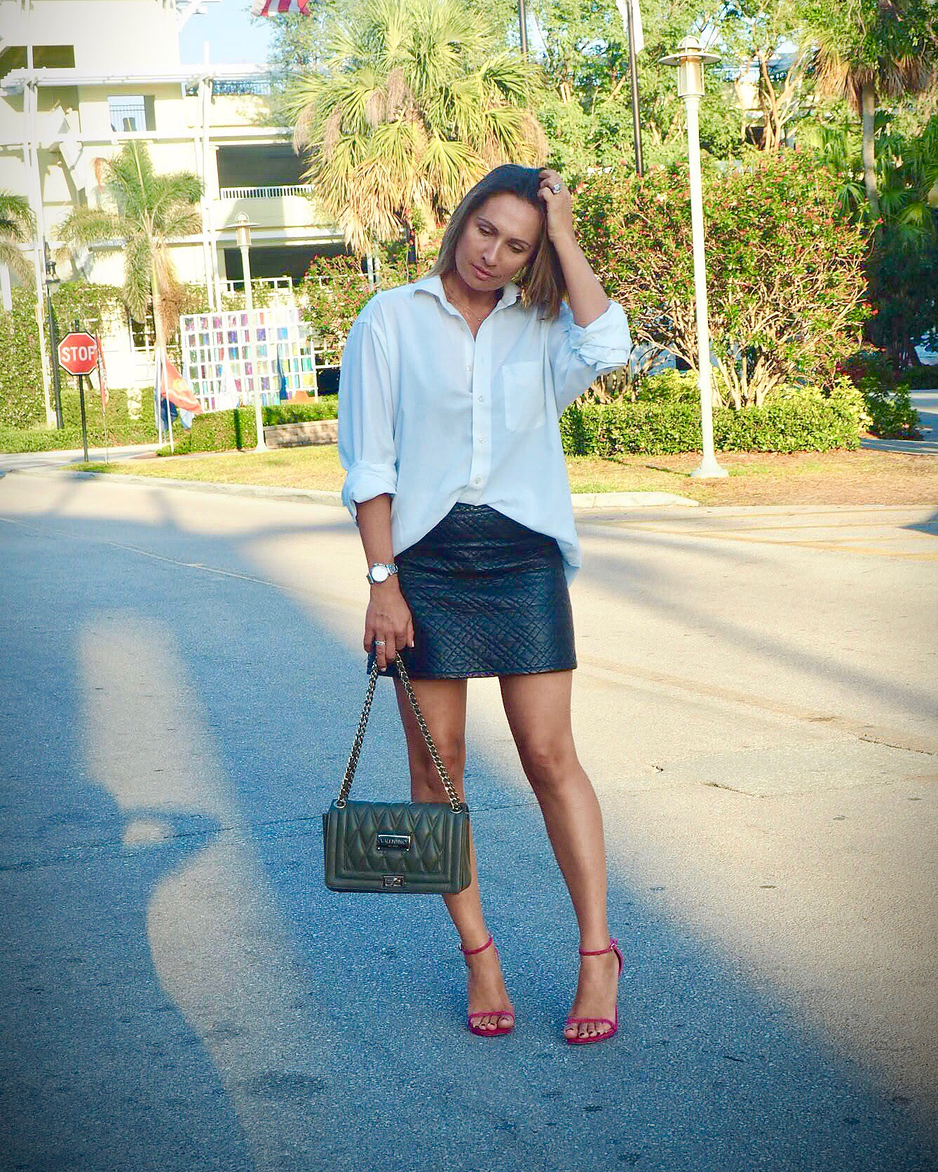 Claire Elizabeth standing in the street in Naples, Florida wearing men's oversized white shirt tucked into black faux leather skirt and hot pink sandals by Stuart Weitzman.
