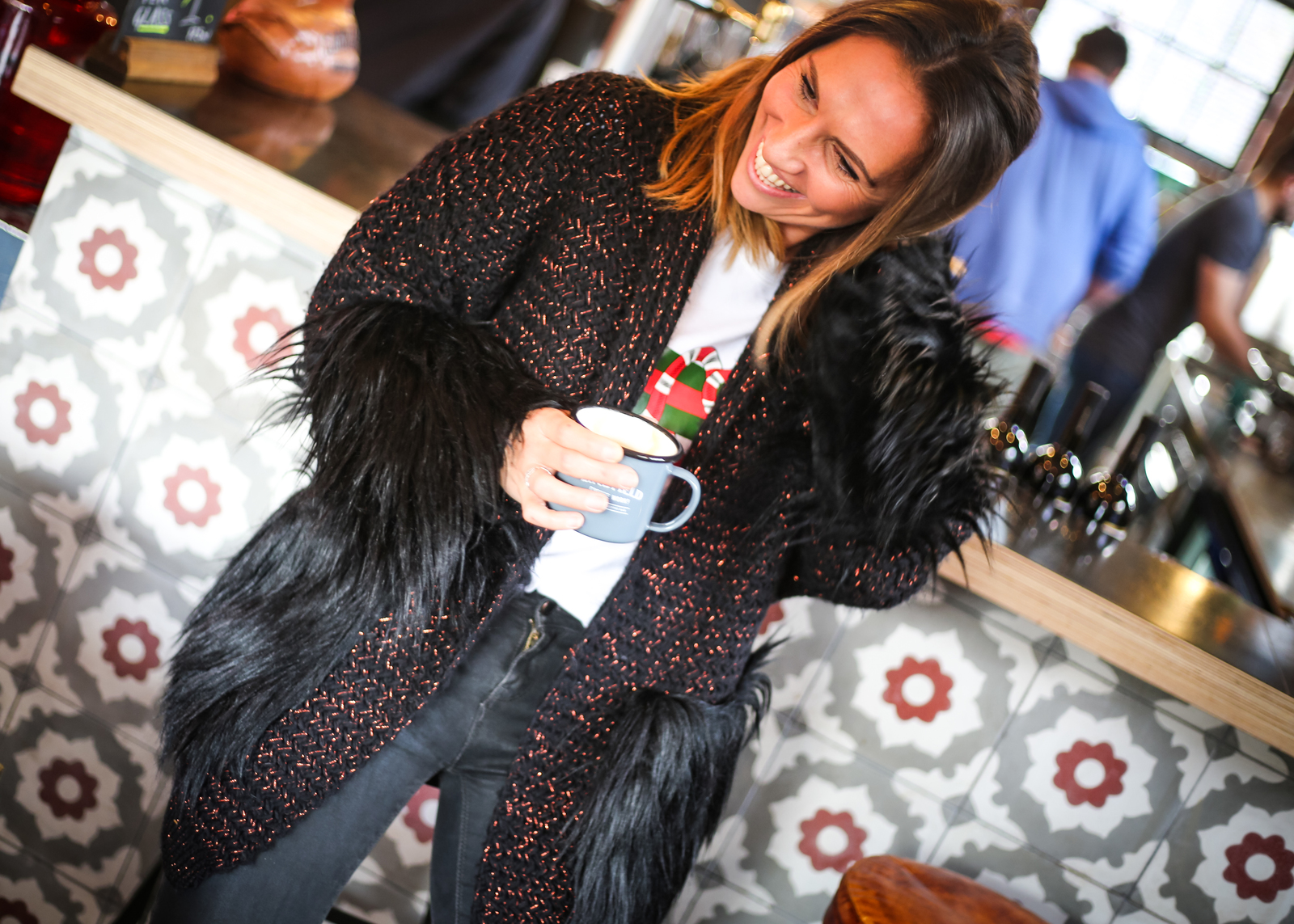 Claire Elizabeth standing holding a coffee cup in Lindfield Coffee works wearing black Faux Fur trimmed coatigan and laughing