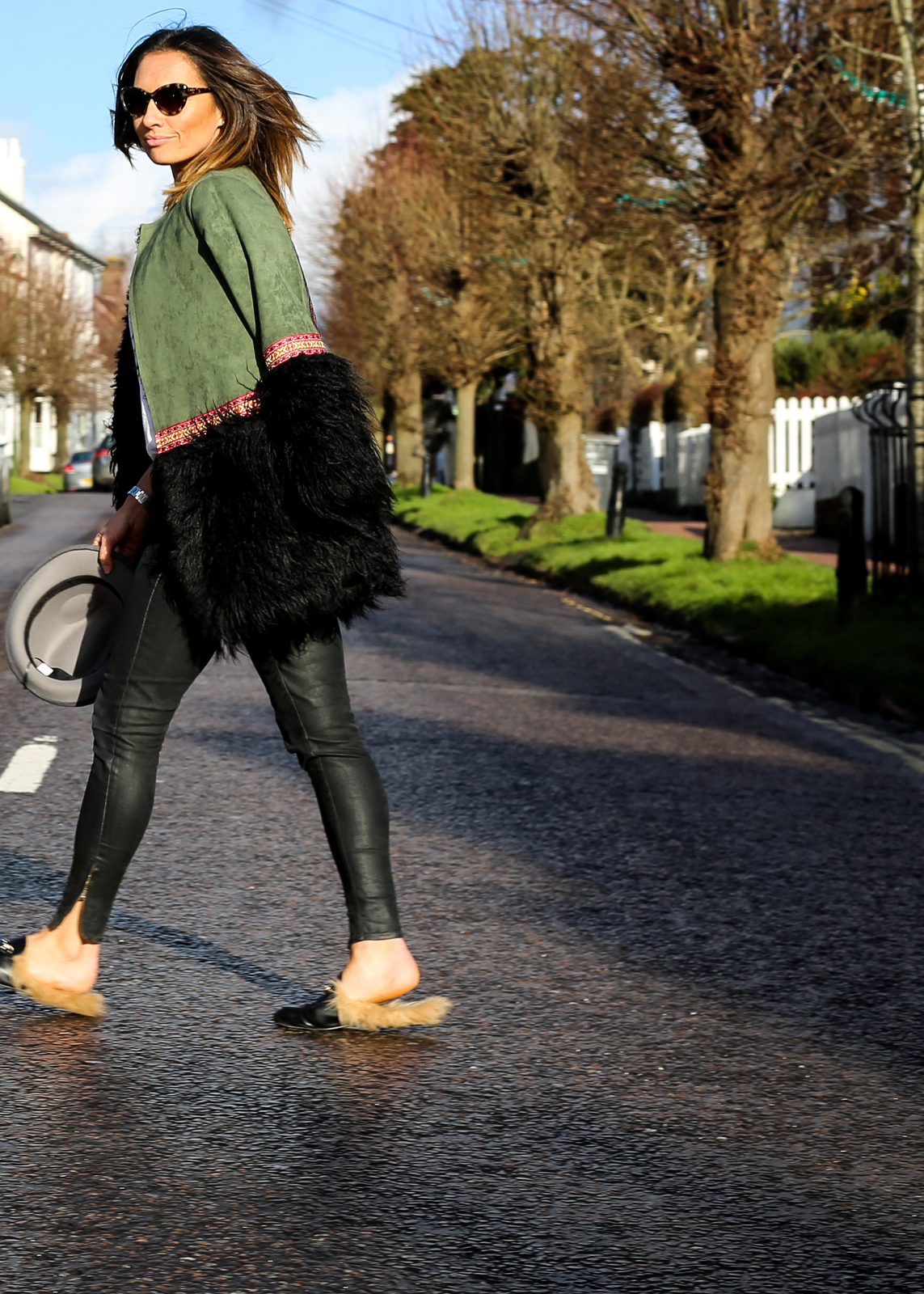 Claire Elizabeth walking across the road wearing leather trousers and green coat with black faux fur trim and Taylor Morris sunglasses