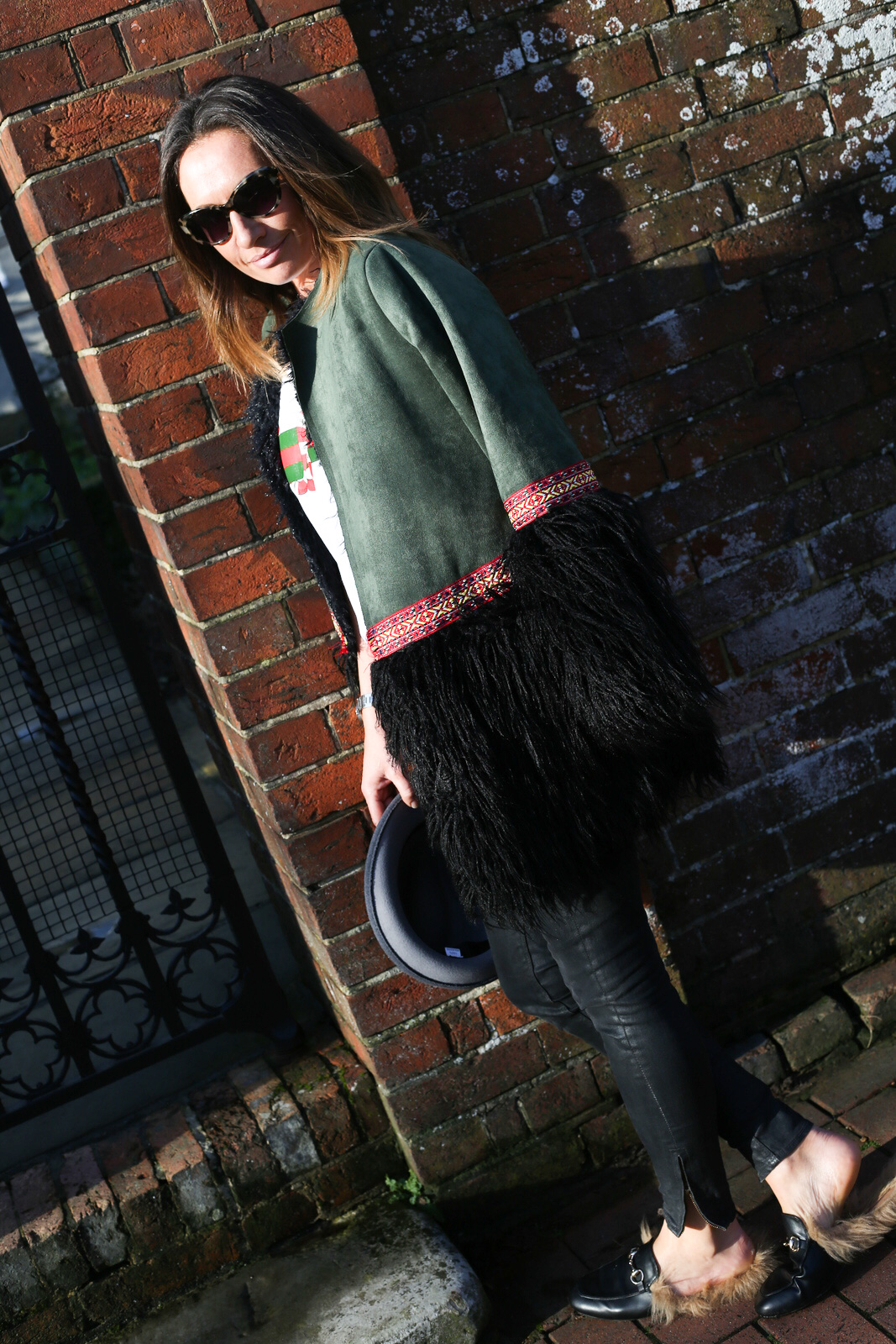 Claire Elizabeth leaning up against a wall wearing green coat with faux fur trim and Taylor Morris sunglasses