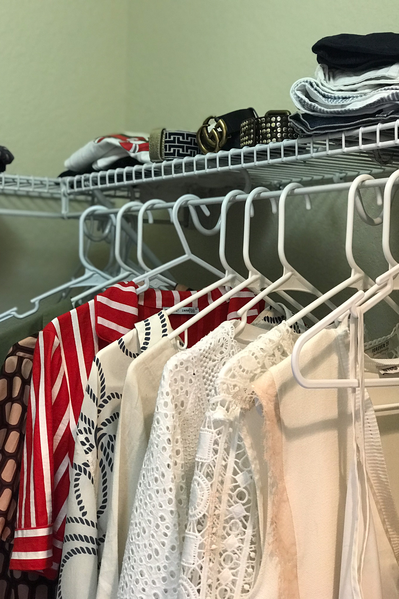 Walk in closet filled with hanging clothes ina variety of colours and styles