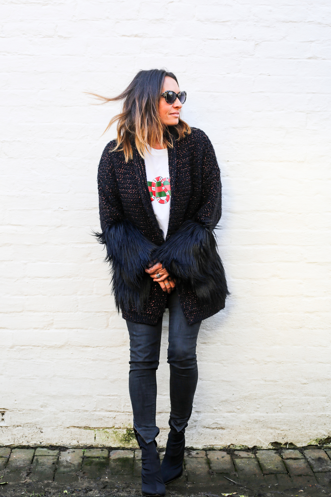 Claire Elizabeth wearing black faux fur trimmed coatigan black leather trousers and Taylor Morris sunglasses while leaning back against a white wall