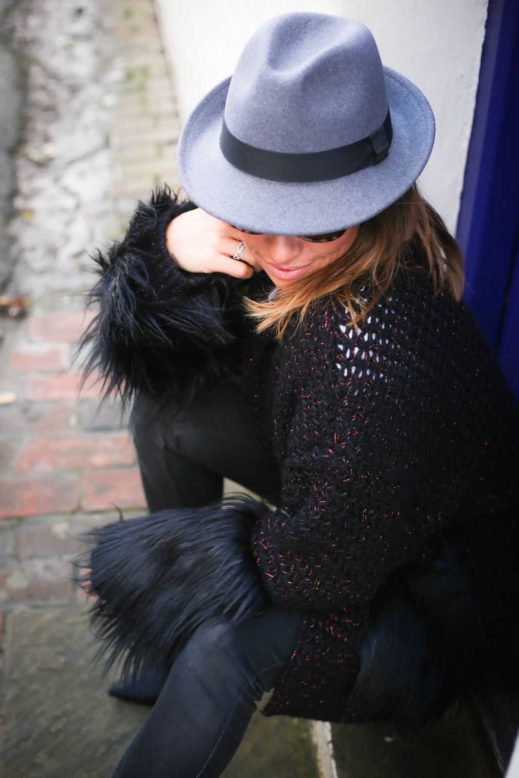 Claire Elizabeth wearing black faux fur trimmed coatigan black leather trousers and Taylor Morris sunglasses sitting on a step in front of a blue door