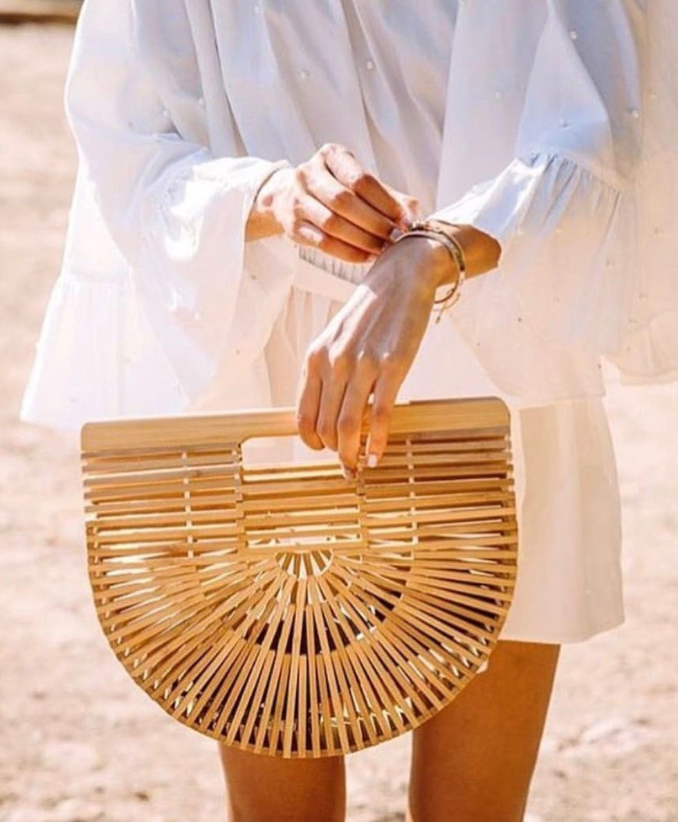 Cult Gaia bamboo bag held by a fashion blogger wearing white shirt dress and gold bracelets