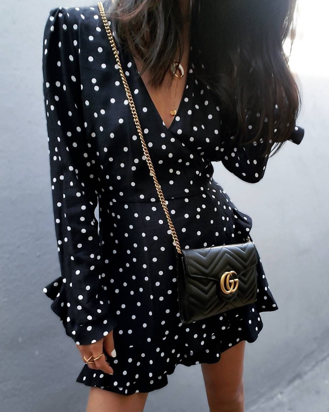 Mini black and white polka dot dress with frill sleeves and a cross body Gucci bag