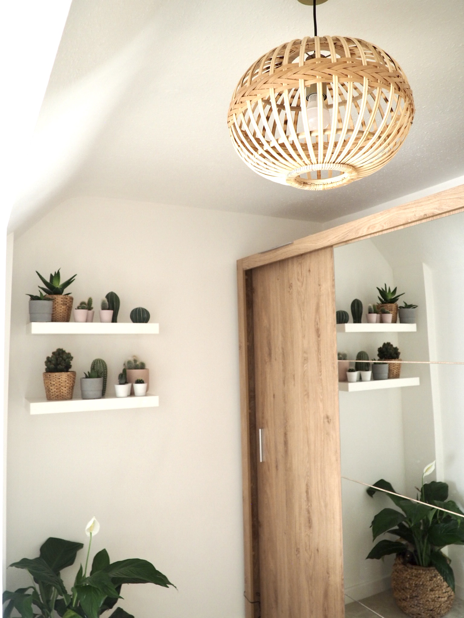 Bamboo pendant light by Wayfair hanging near the Instrument London wood wardrobes and the shelves with cactuses on.
